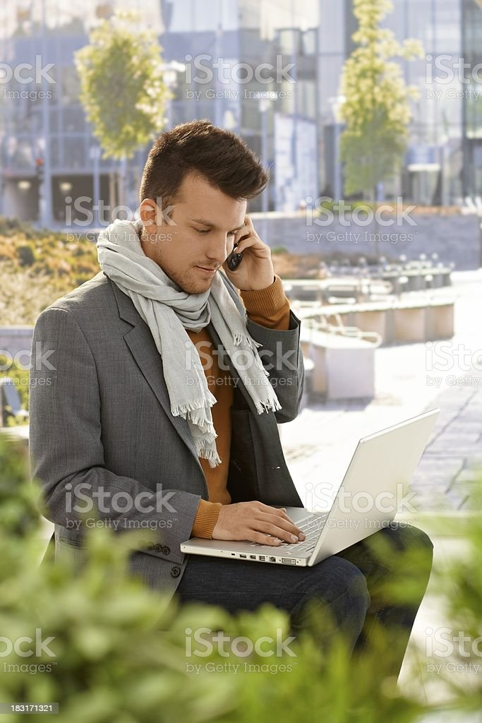 Young man with mobile and laptop outdoors royalty-free stock photo