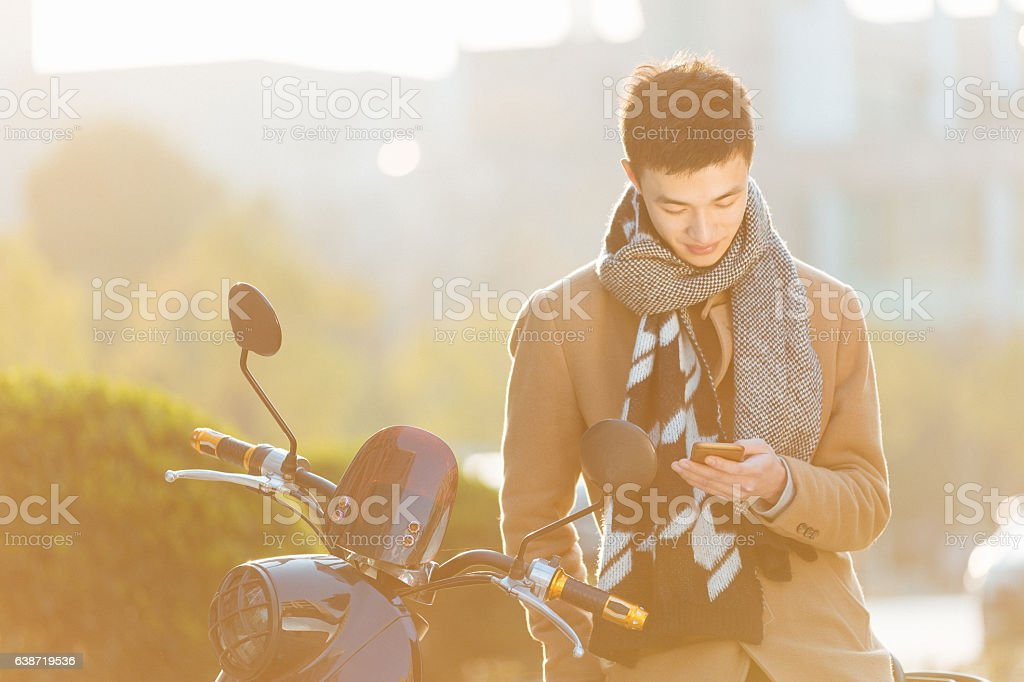 young man with mobile phone on motorcycle in modern city stock photo