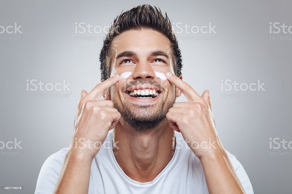 Young man with moisturizer on the face stock photo