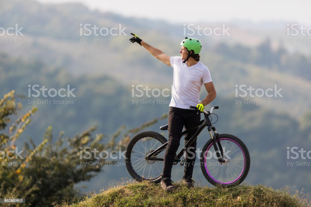 Young man with mountain bicycle pointing at the distance. stock photo