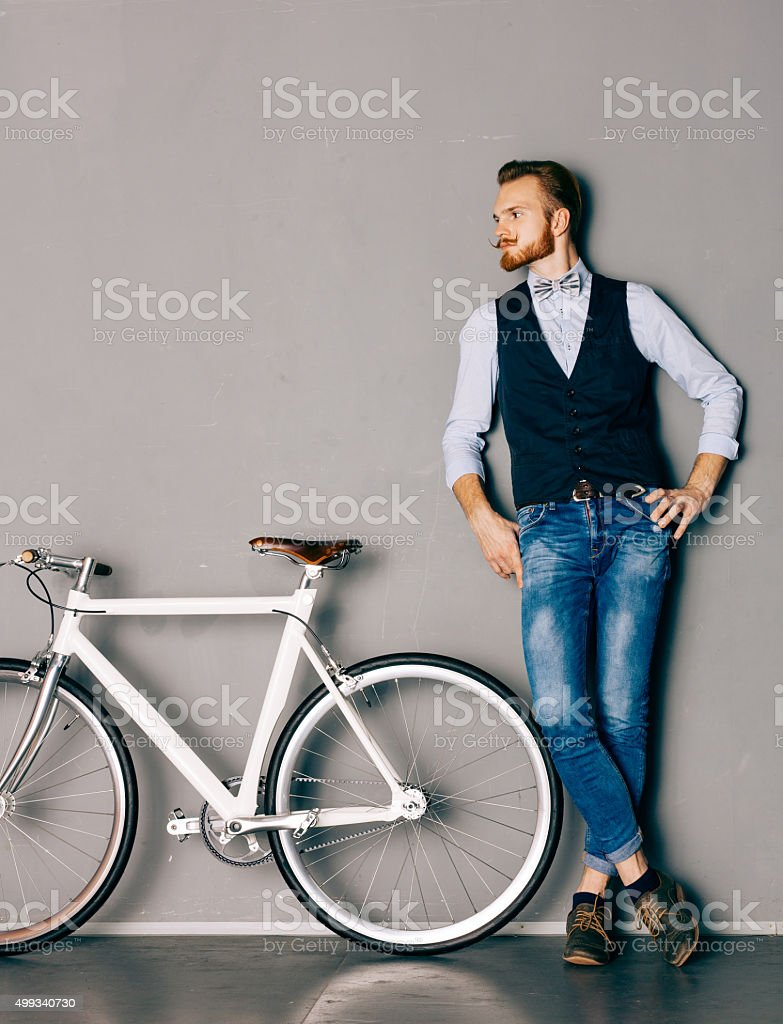 Young man with mustache and beard is near bicycle stock photo