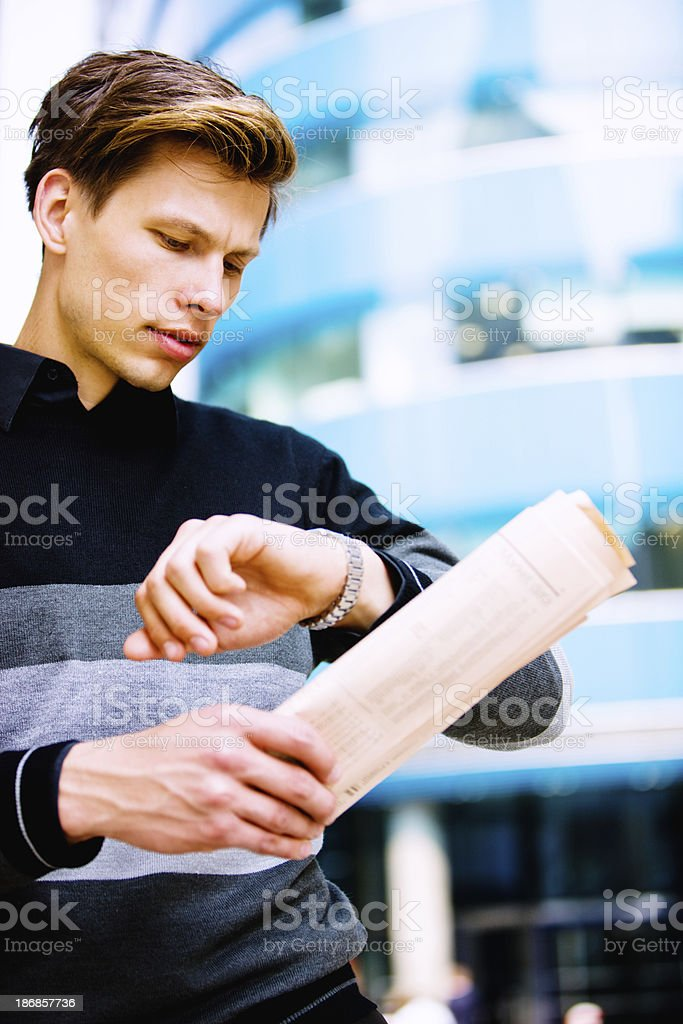 Young Man with newspaper checking time, London royalty-free stock photo