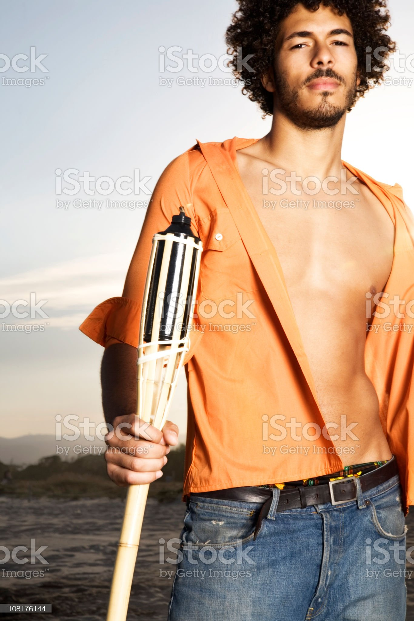 Young Man With Open Shirt Holding Tiki Torch at Beach royalty-free stock photo