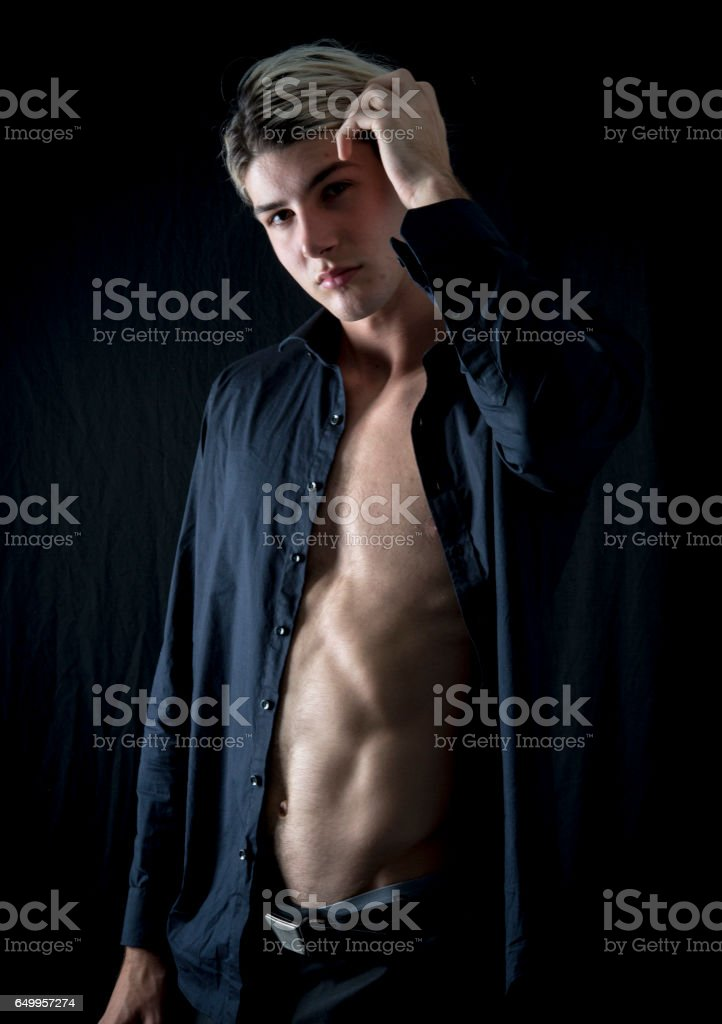 young man with open shirt pushes back his hair. stock photo