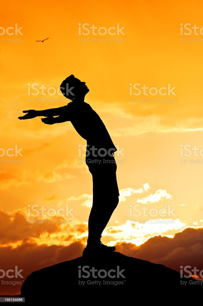 Young man with outstretched arms, sunset scenery after storm (II) royalty-free stock photo