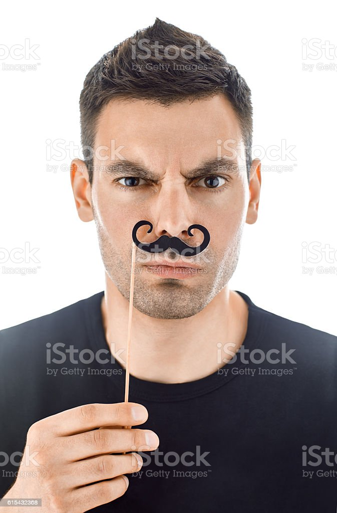 Young man with paper moustaches making faces stock photo