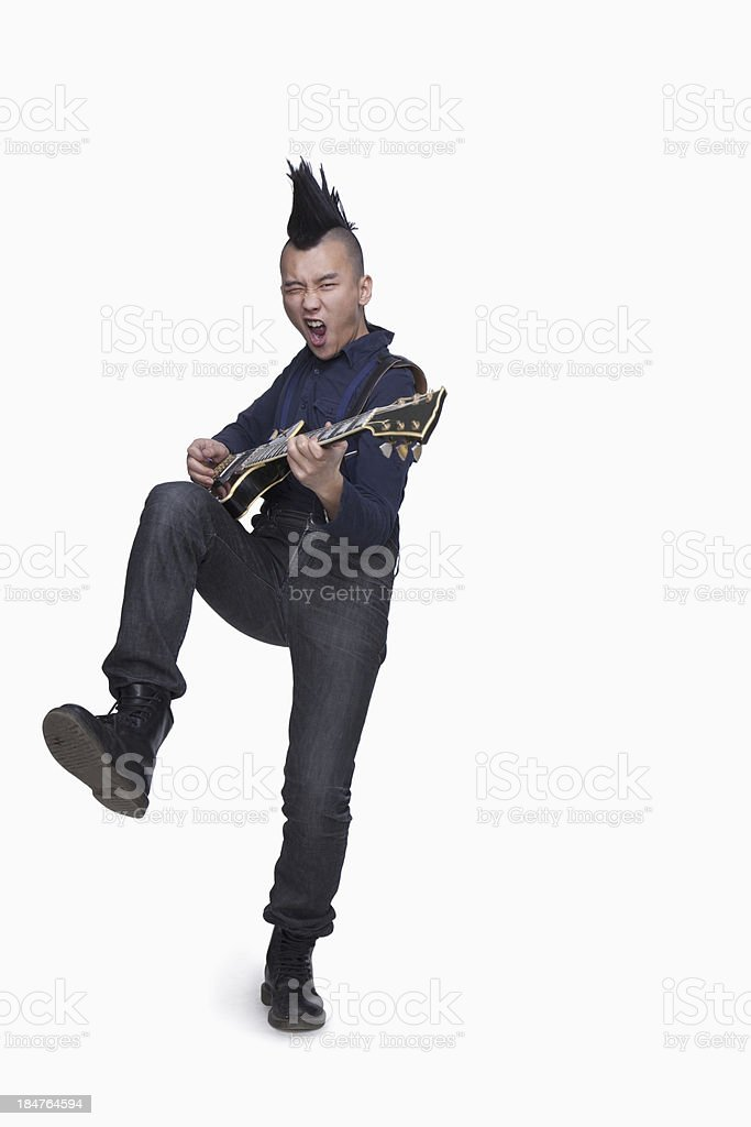 Young man with punk Mohawk playing guitar stock photo