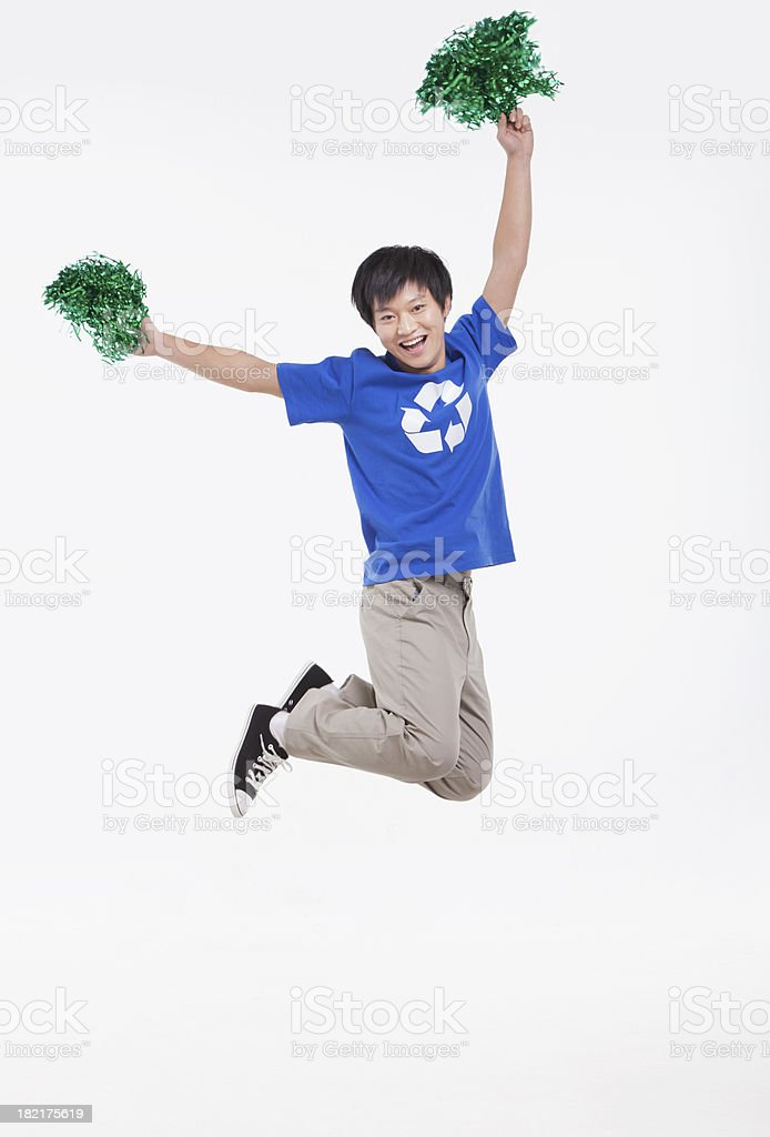 Young man with recycling t-shirt and pompoms cheering, studio shot royalty-free stock photo