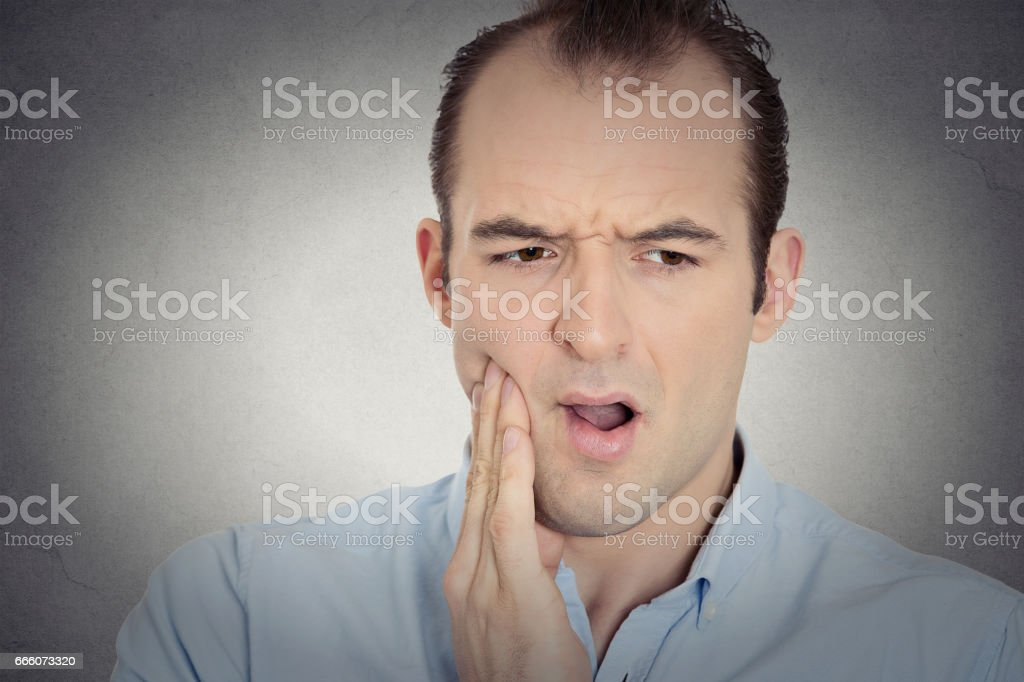 young man with sensitive tooth ache crown problem suffering from pain stock photo