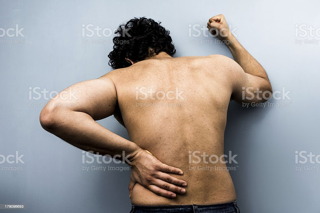 Young man with severe backpain from sciatica royalty-free stock photo