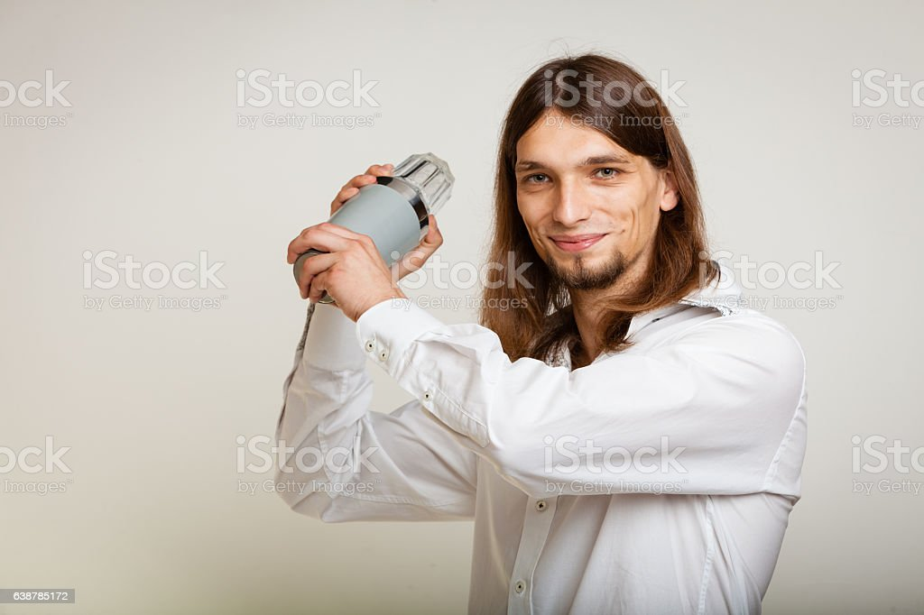 Young man with shaker making cocktail drink stock photo