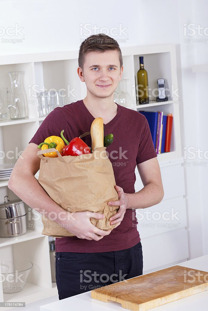 Young man with shopping bag in the kitchen royalty-free stock photo