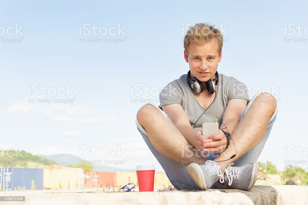 Young man with smartphone and headphones stock photo