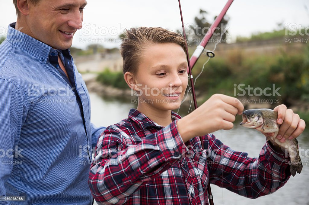 Young man with son looking at fish on hook stock photo