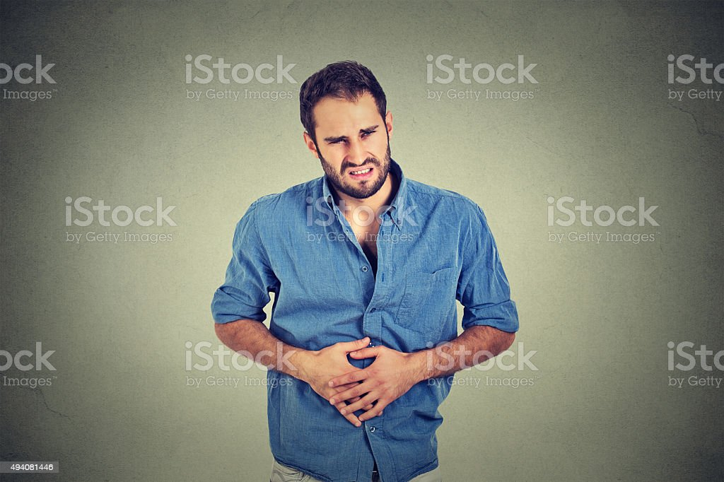 Young man with stomach pain indigestion stock photo