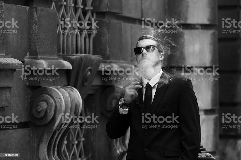 Young man with sunglasses and black suit stock photo