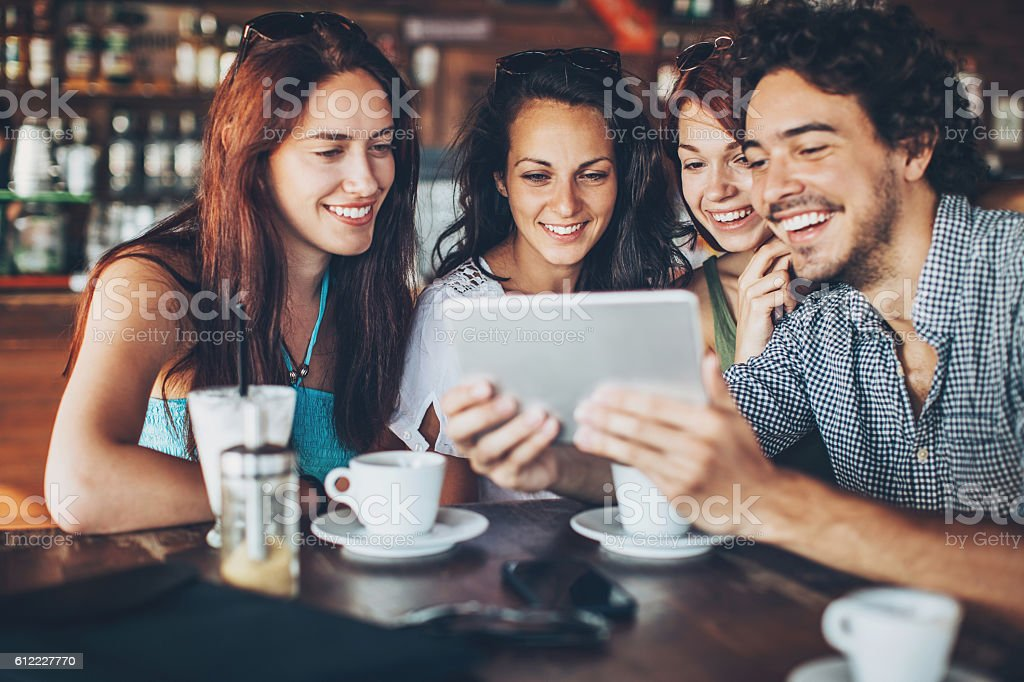 Young man with tablet showing pictures to group of girls stock photo