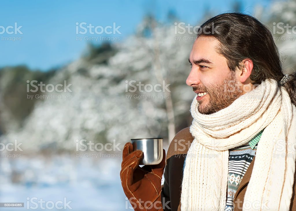 young man with tea standing in snowy woods stock photo