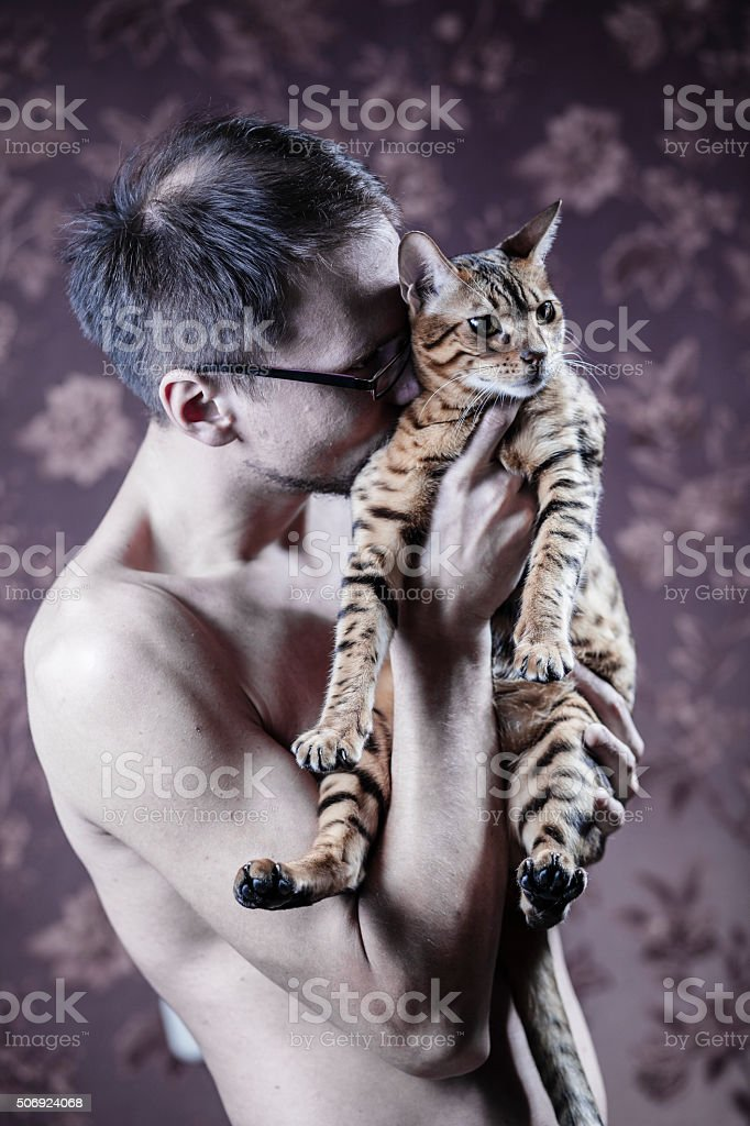 Young man with the bengal cat stock photo