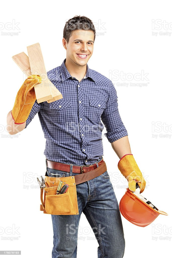 Young man with tool belt holding hard hat and wooden planks royalty-free stock photo