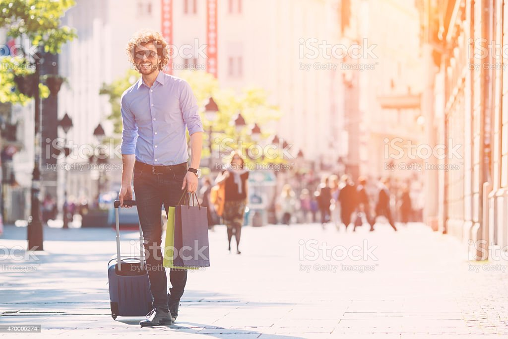 Young Man With Trolley Bag Walking in a city. stock photo