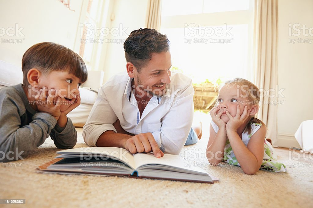 Young man with two kids reading a story book stock photo