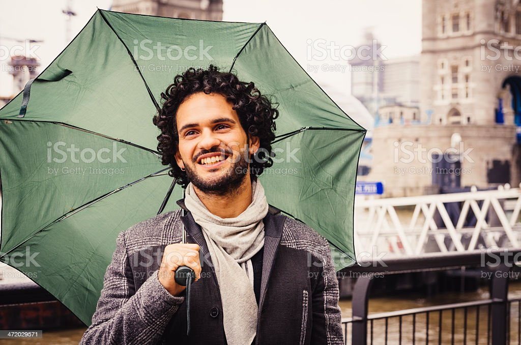 Young Man With Umbrella Near Tower Bridge In London stock photo