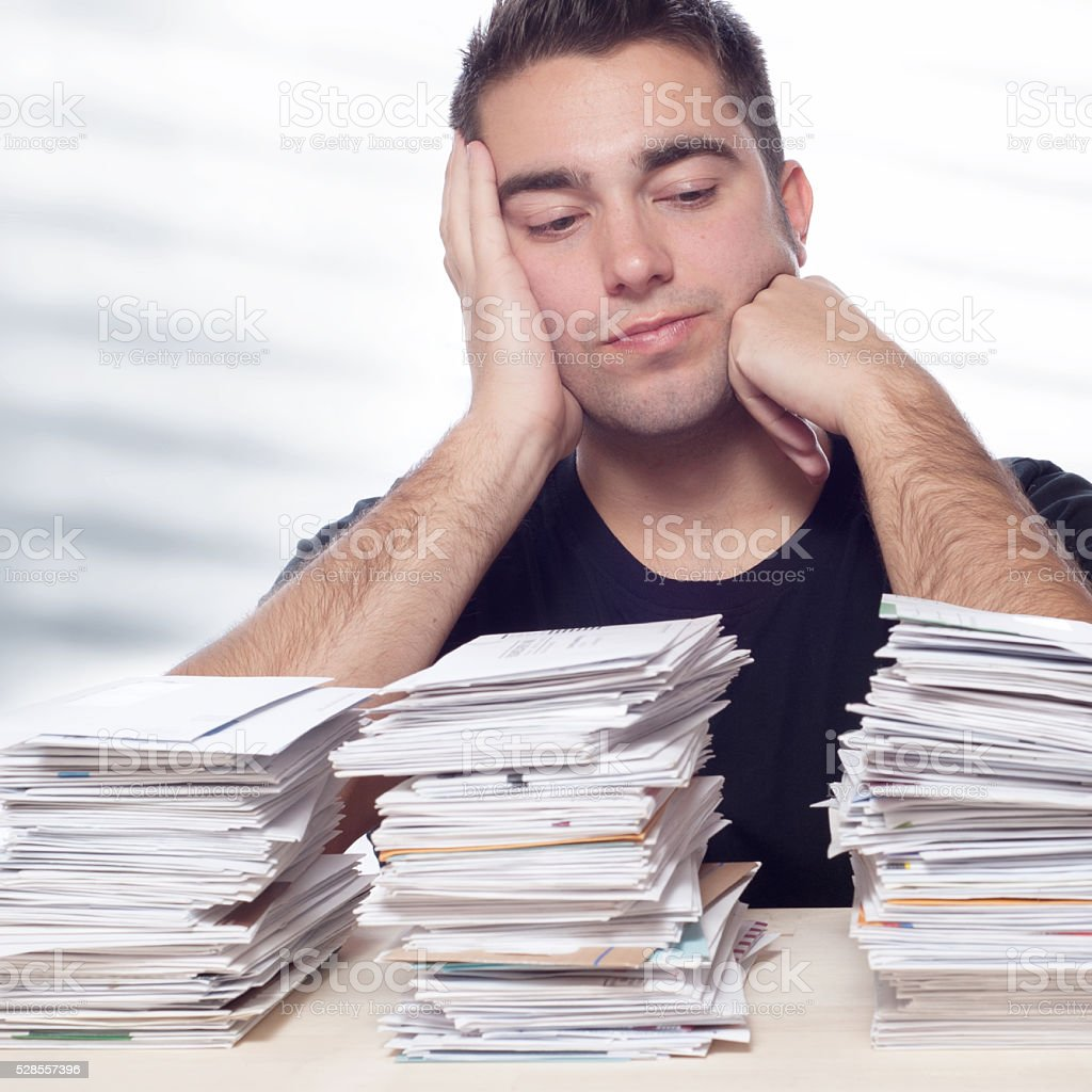Young Man with Unpaid Mortagage, Studen Loan, Credit Card Bills stock photo