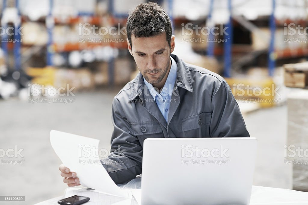 Young man with white laptop, holding paper royalty-free stock photo