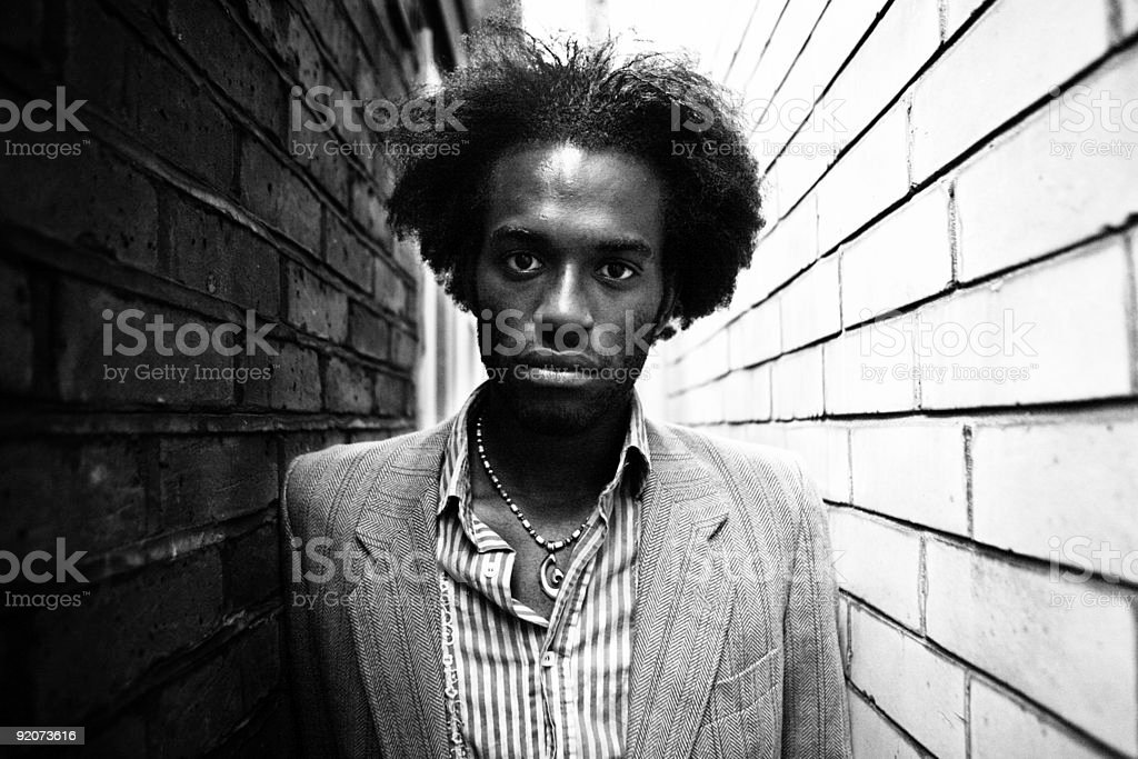 Young Man with Wild Hair Between Brick Walls royalty-free stock photo