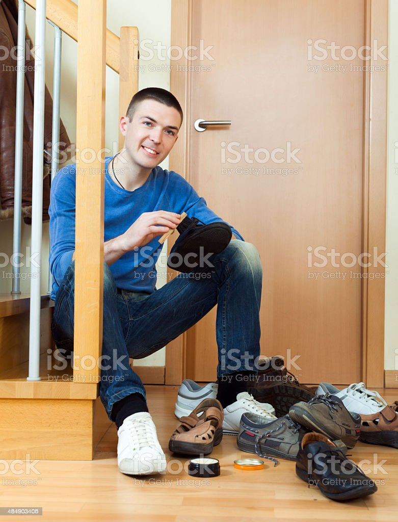 Young man woman cleaning shoes stock photo