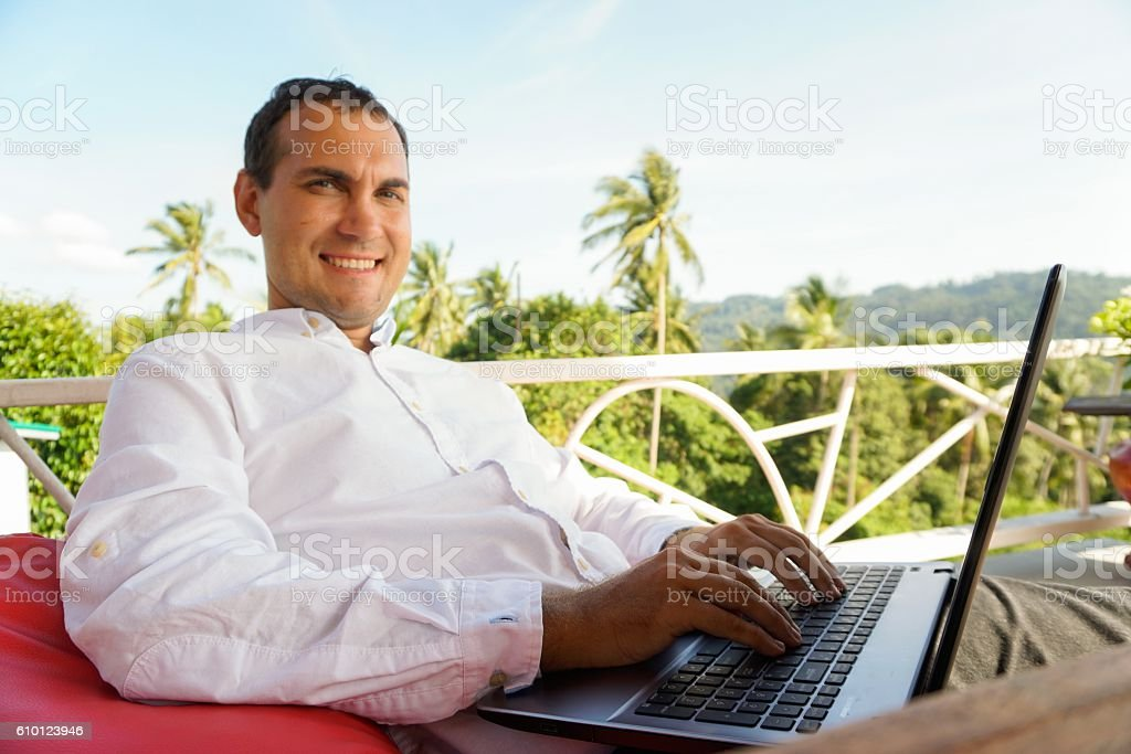 Young man work with laptop relaxing on tropical terrace stock photo