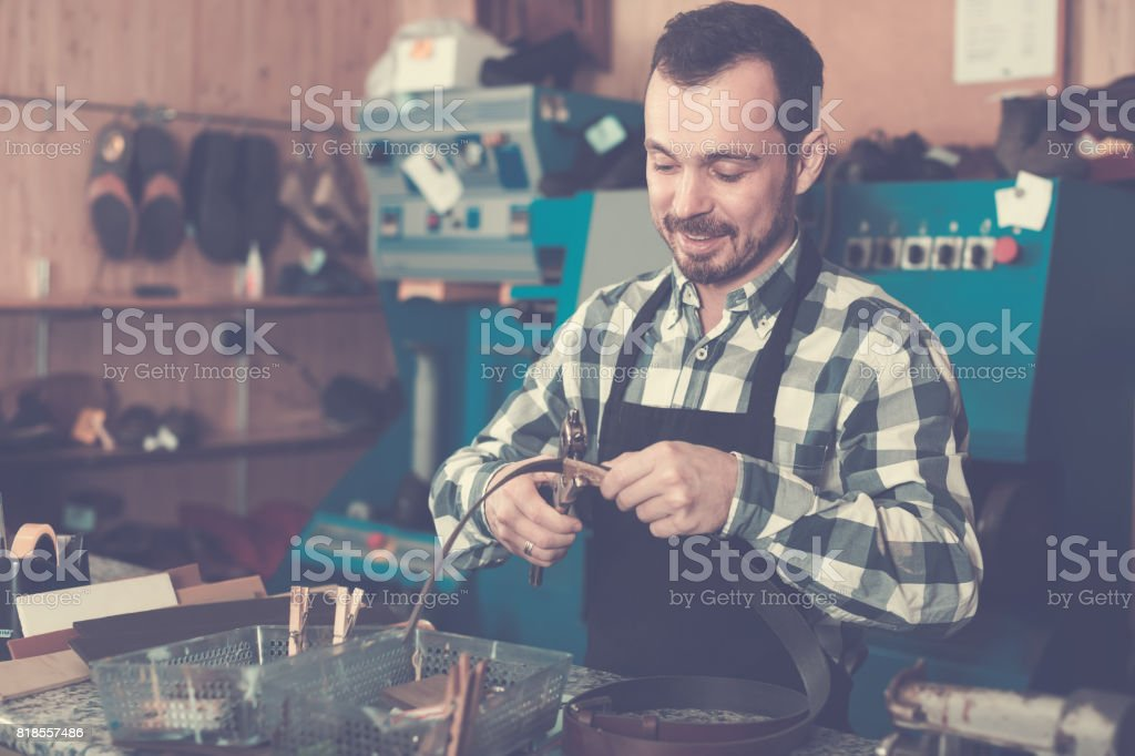 Young man worker working at forming hole in belt stock photo