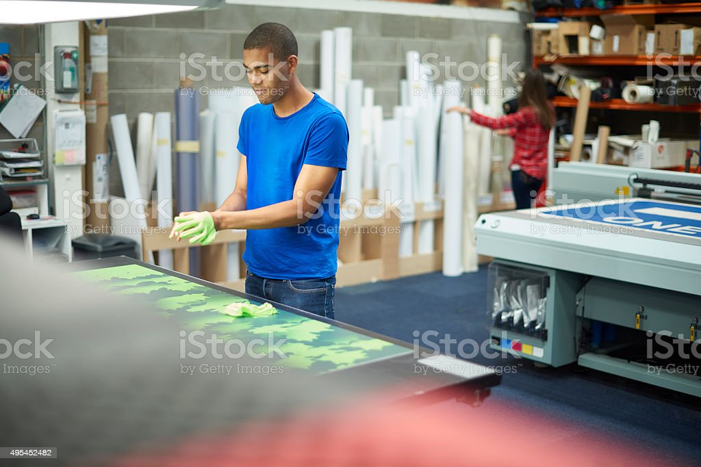 young man working at a signage company stock photo