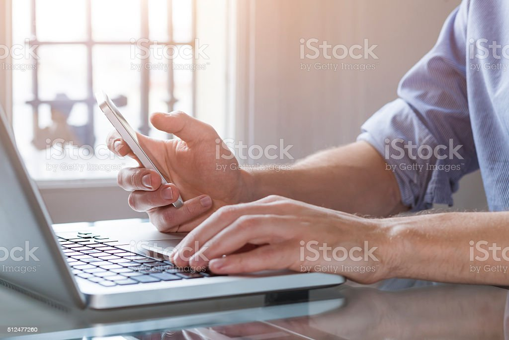 Young man working from home with laptop computer and smartphone stock photo