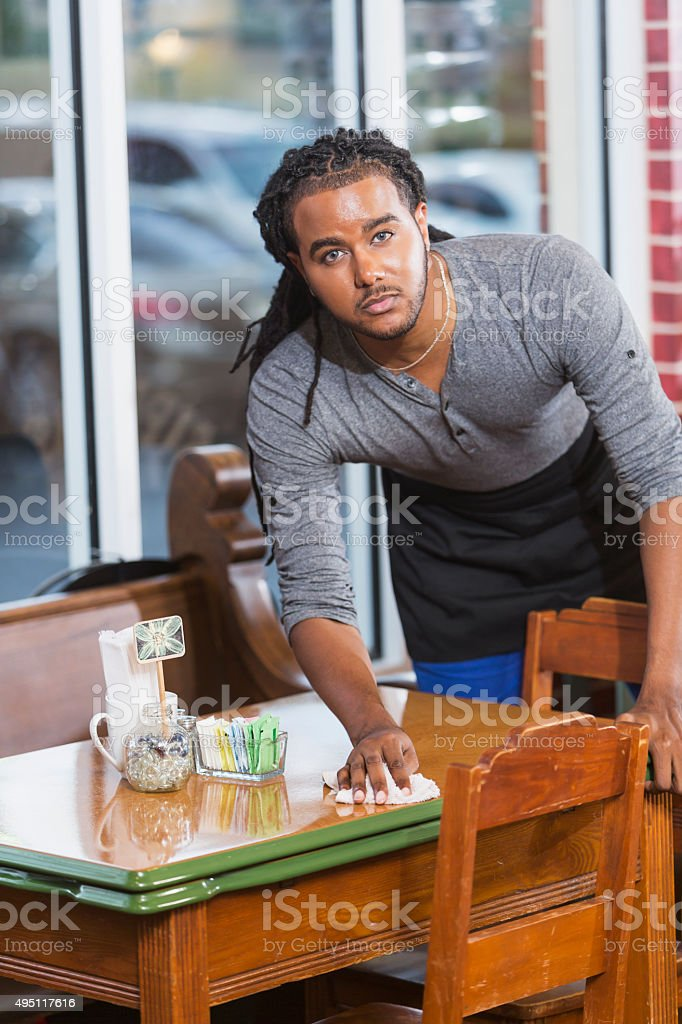 Young man working in restaurant cleaning table stock photo