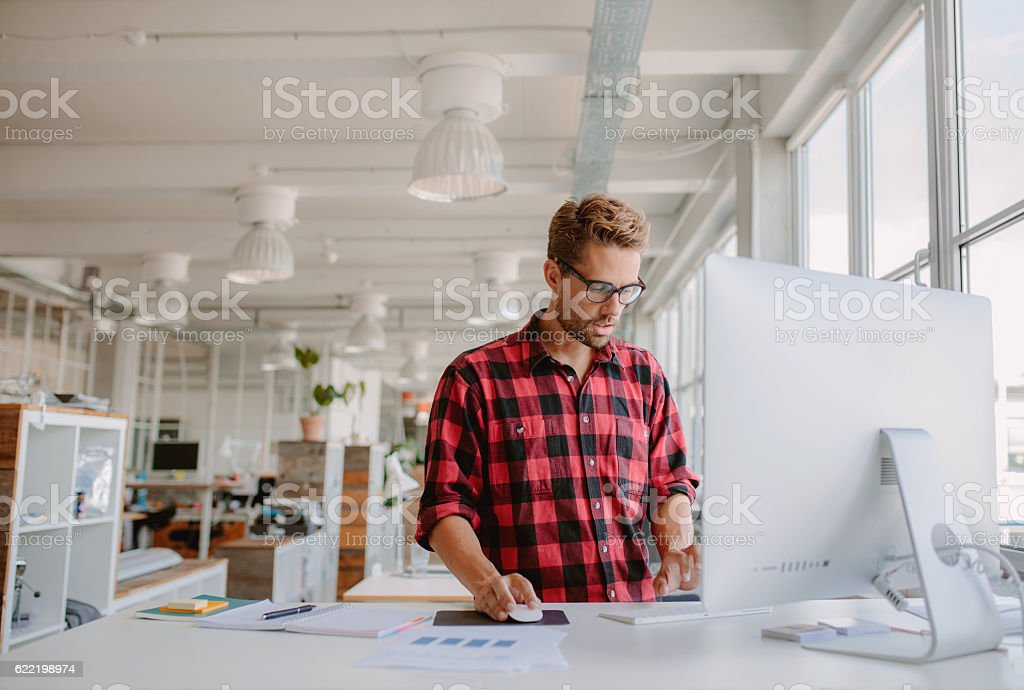 Young man working on computer in modern office stock photo