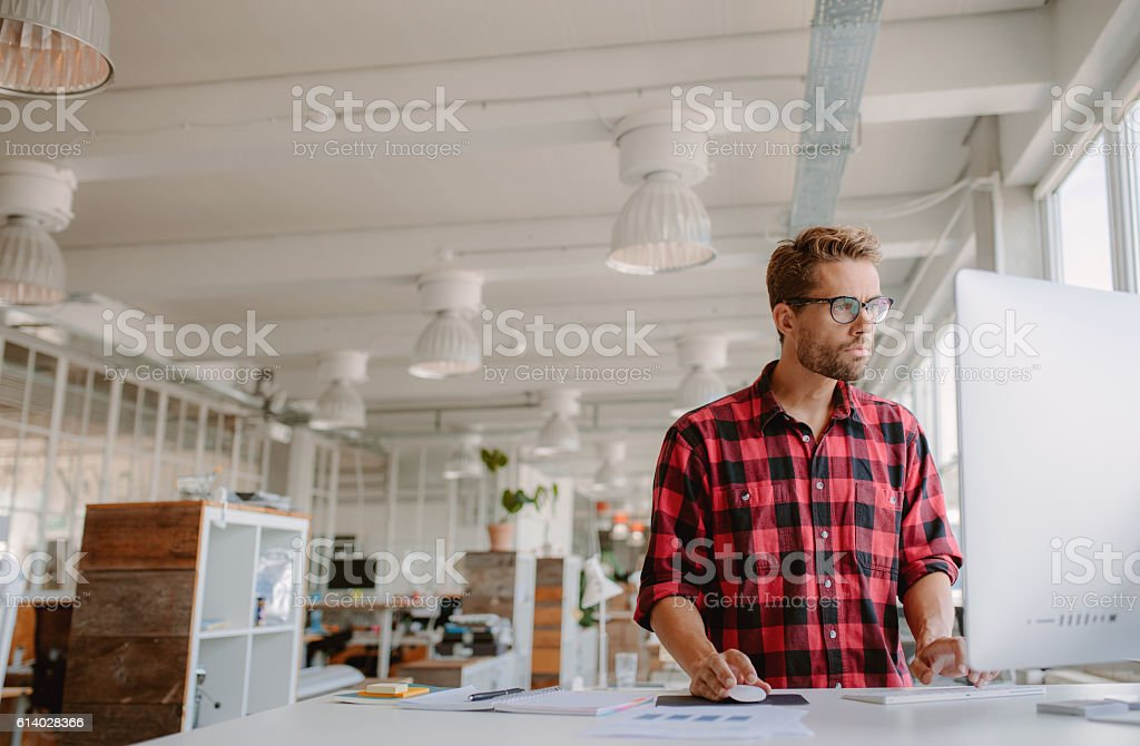 Young man working on computer in modern workplace stock photo