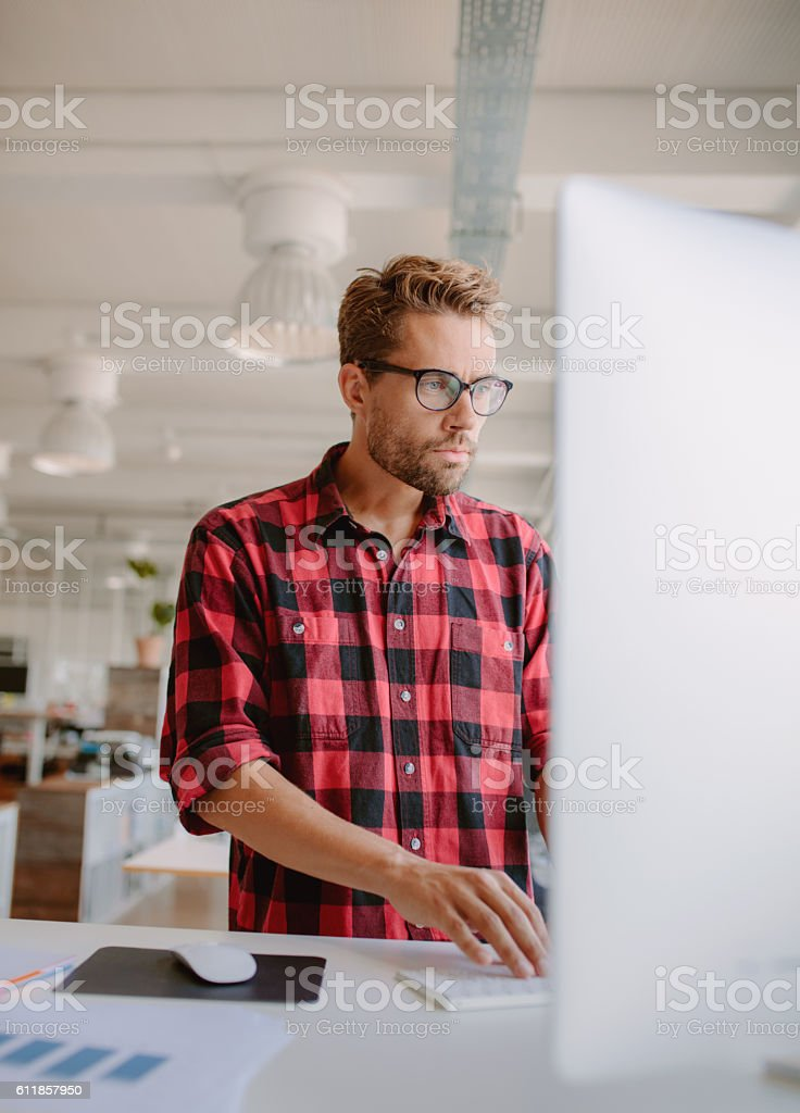 Young man working on computer in office stock photo