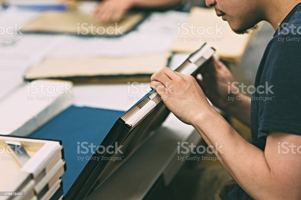 Young man working on frames and canvases. stock photo