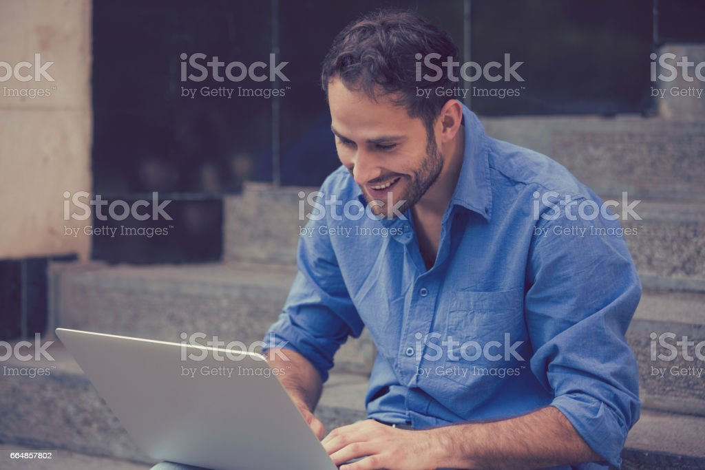 young man working on laptop outdoors sitting on steps outside of his office stock photo