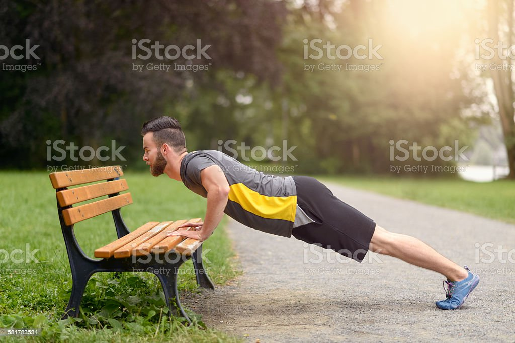 Young man working out doing push-ups stock photo