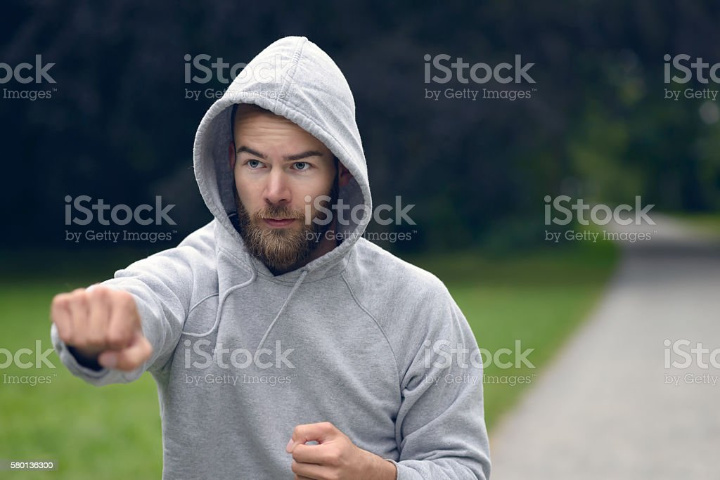 Young man working out in a park punching air stock photo
