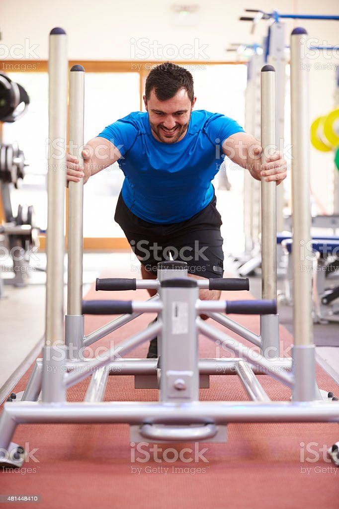 Young man working out using equipment at a gym, vertical stock photo
