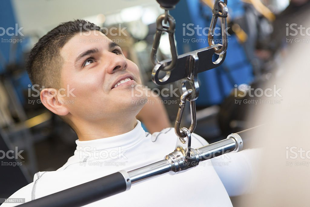 Young man working out with weight machine at the gym royalty-free stock photo