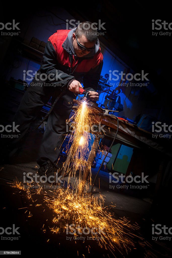 Young man working with plasma cutter on steel plate stock photo