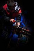 Young man working with plasma cutter on steel plate