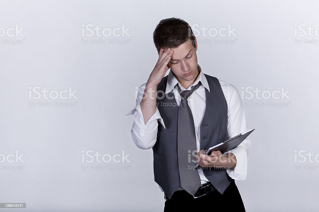 Young man worried looking at clipboard royalty-free stock photo