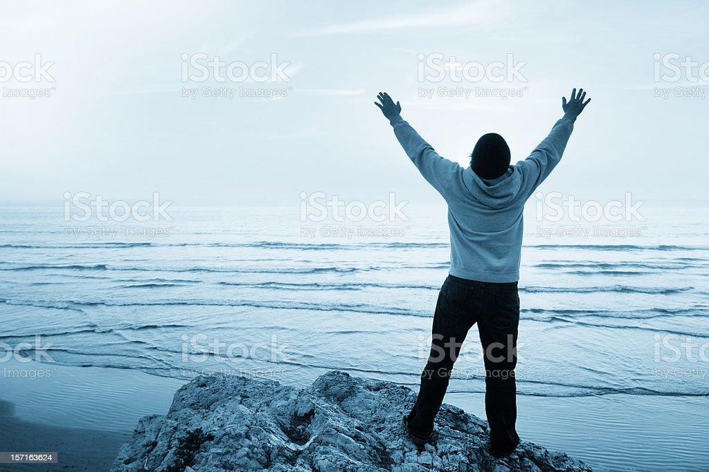 Young Man Worshiping at the Beach stock photo