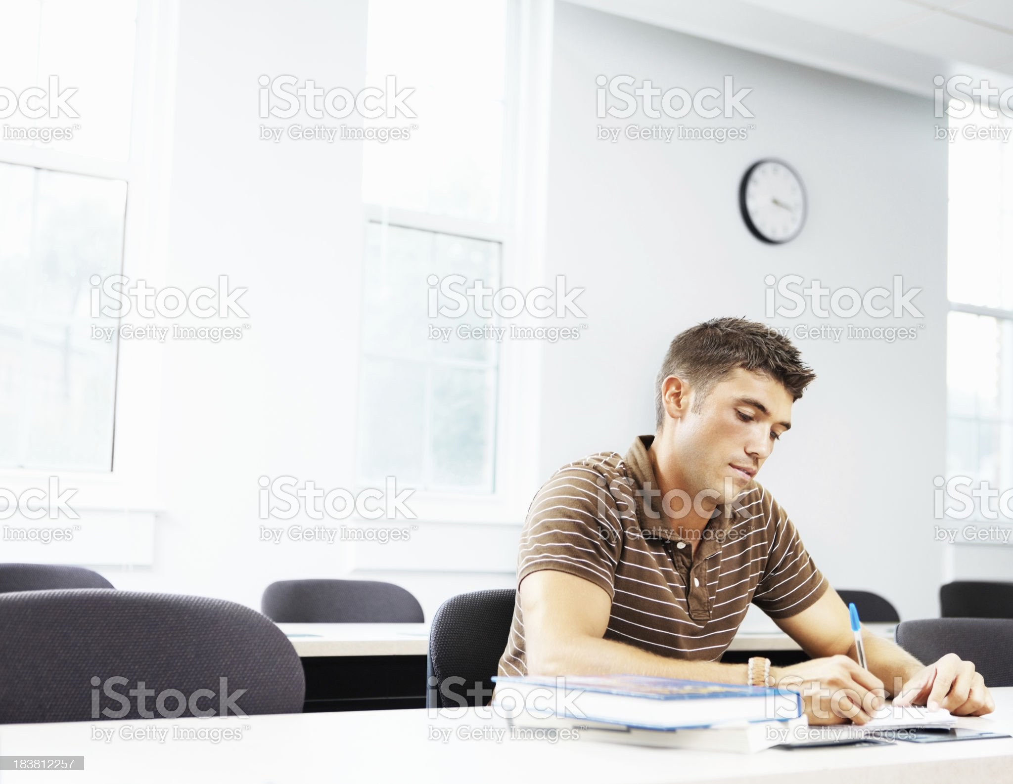 Young man writing notes in classroom royalty-free stock photo